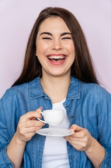 Женщина смеется за чашкой кофе