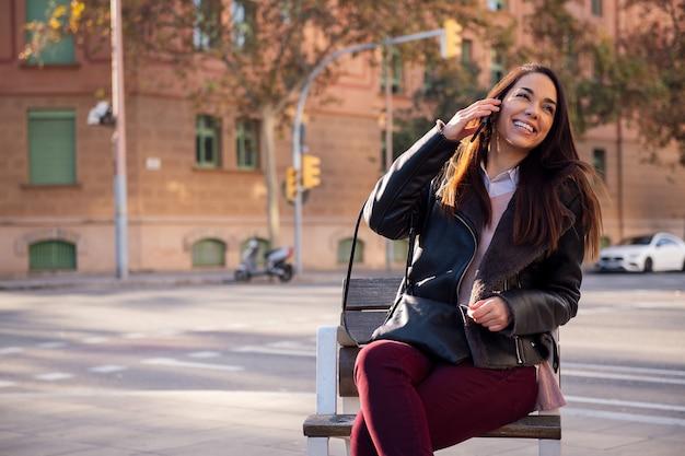 Женщина смеется во время звонка на улице