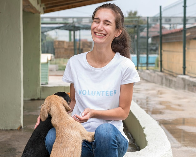 Woman laughing while playing with rescue dogs at shelter