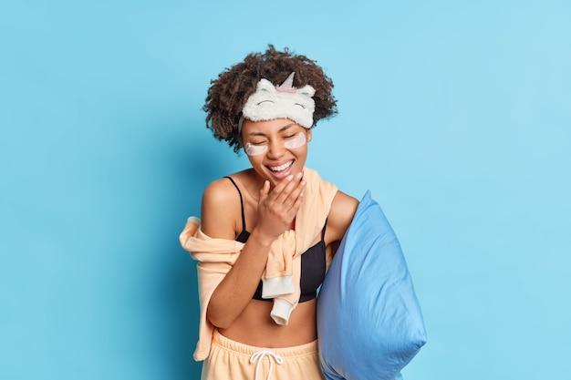 寝間着の服を着て枕を着て寝る前に騙された面白い話を聞いて女性は笑い、青い壁に隔離された美容処置を受けます