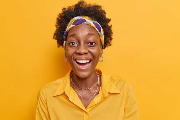 Woman laughs positively watches something funny looks upbeat hears funny joke dressed in stylish outfit poses on yellow