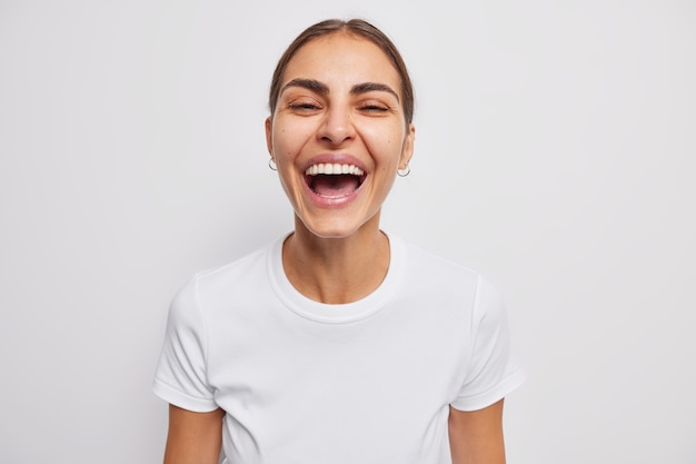 女性は真摯に笑い、白い笑顔でカジュアルなtシャツを着た前向きな感情を表現します。