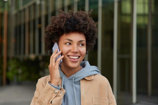 로밍에서 스마트폰 통화를 하는 동안 여성은 캐주얼 옷을 입고 곱슬머리를 하고 밖에서 포즈를 취하는 동안 웃는다
