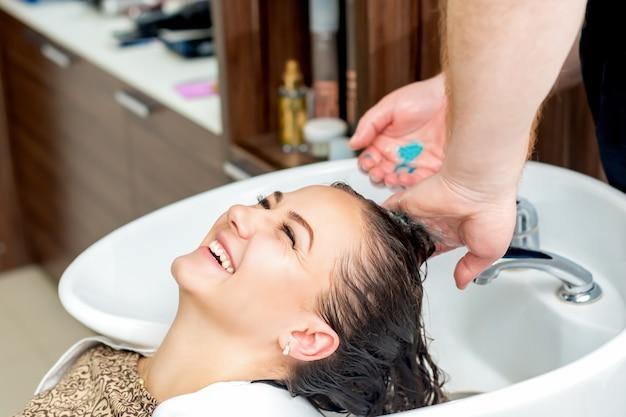 Женщина смеется, мытье волос в раковине в салоне.