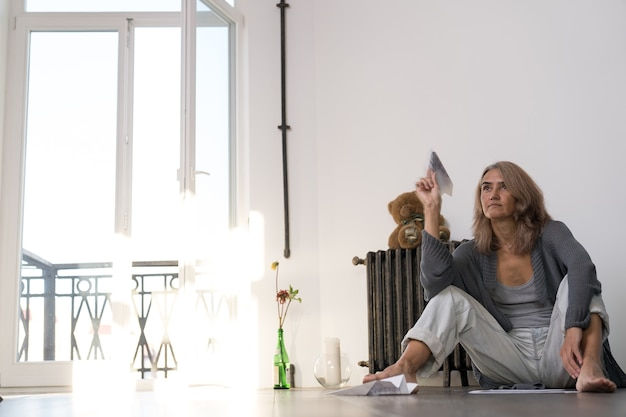 Woman launches into a paper plane in her apartment