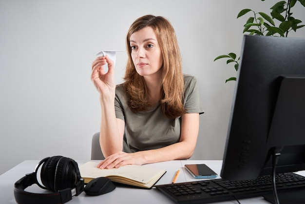 Woman launches paper plane and dreaming about vacation while sitting at computer at remote work