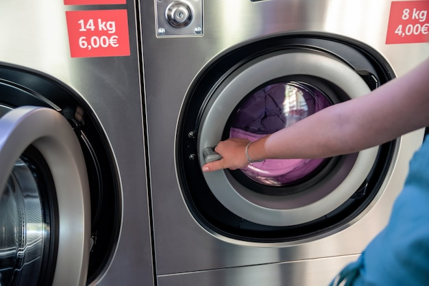 Woman in a laundromat. woman's hand closing the door of an industrial washing machine.