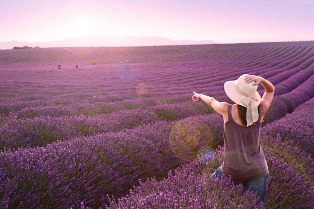 Woman on lavender field on pink sunset