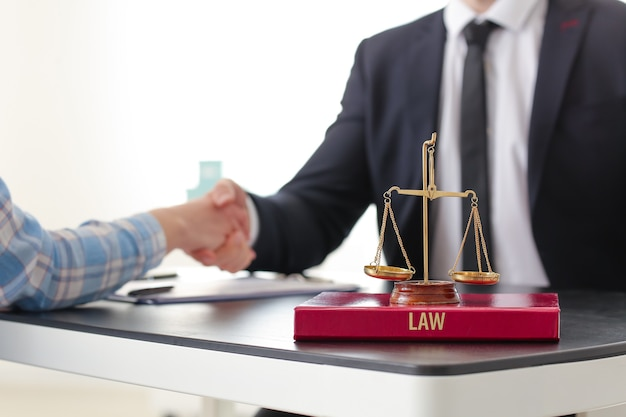 Woman and lawyer shaking hands in office