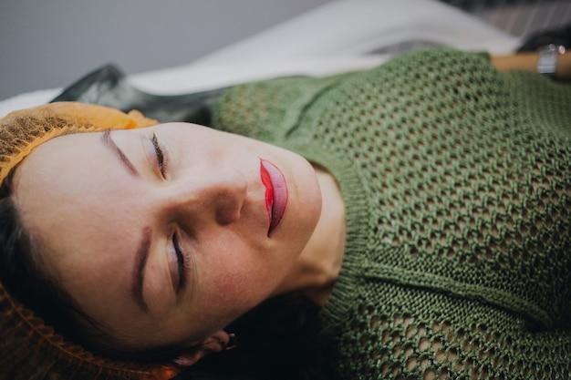 Женщина лежала в салоне красоты для процедуры перманентного макияжа губ