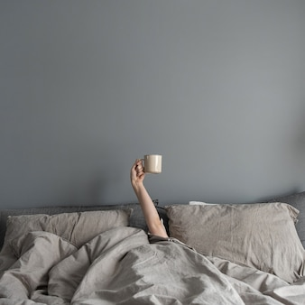 Woman laying in bed and holding mug with coffee with hand.