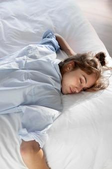 Donna che risiede nel colpo medio del letto