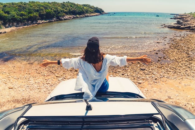 Woman laying at car hood with view of sea summer beach vacation copy space