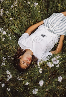 Woman laying down in a daisy field wearing a white graphic t-shirt