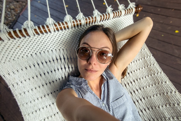 Woman laying in hammock pov vacation selfie
