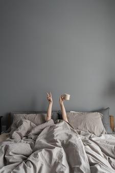 ベッドに横になり、手でコーヒーとマグカップを保持し、勝利のシンボルを表示する女性