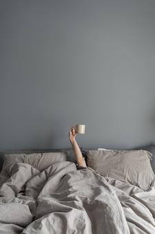 여자가 침대에 누워 손으로 커피 머그잔을 들고