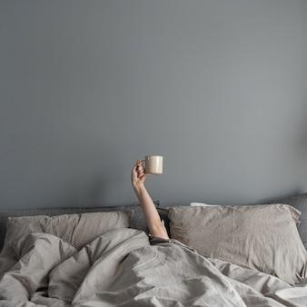 ベッドに横になり、手でコーヒーとマグカップを保持している女性。