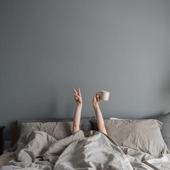 여자가 침대에 누워 커피 머그잔을 손에 들고 승리 기호를 표시