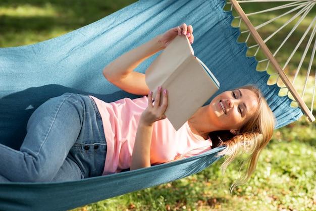 Женщина лежит в гамаке и читает