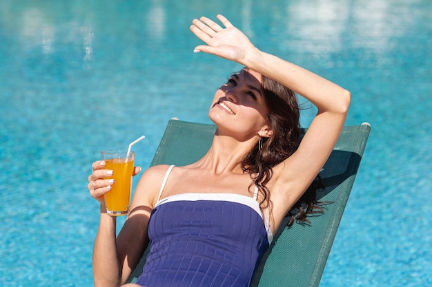 Woman laying on lounge blocking sun with hand