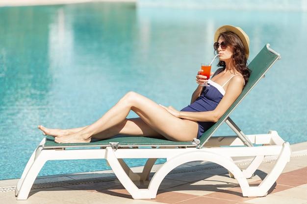 Woman laying on lounge enjoying drink