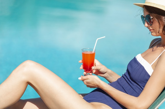 Woman laying on lounge holding drink