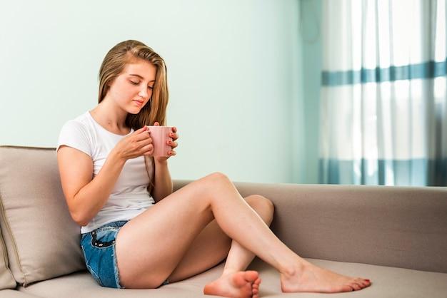 コーヒーを飲みながらソファの上に敷設する女性