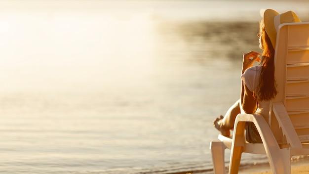 海を見てサンベッドを置く女性