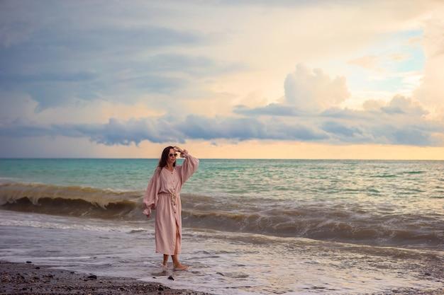 Женщина, лежа на пляже, наслаждаясь летними каникулами, глядя на море