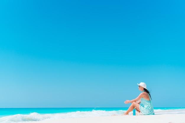 海を見ながら夏休みを楽しんでビーチに横たわる女性