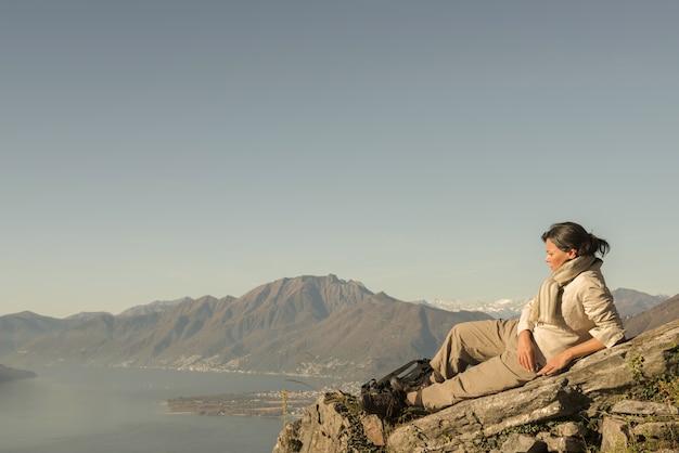 Donna che pone sulla roccia con una bellissima vista di una montagna vicino al mare