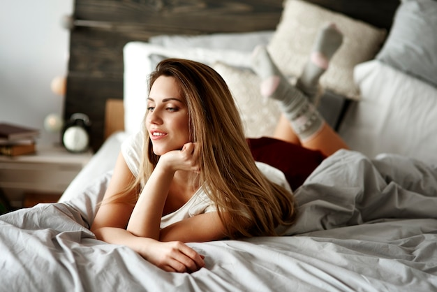 Woman laying on stomach on bed