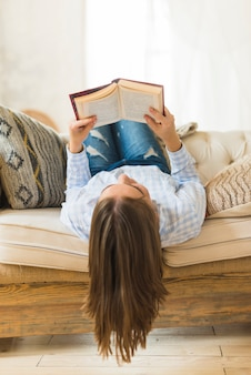 Woman laying upside down on sofa with holding book