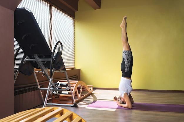 ヨガをしている健康的なライフスタイルをリードする女性は、マットの上で逆アサナsirshasanaポーズを実行します