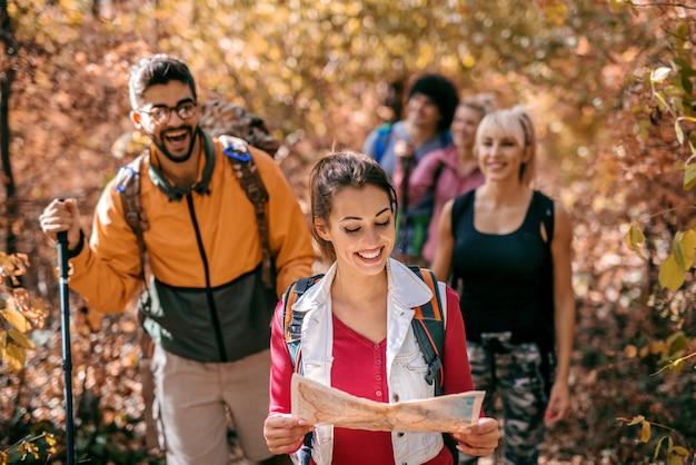 Женщина ведет других туристов в лесу.