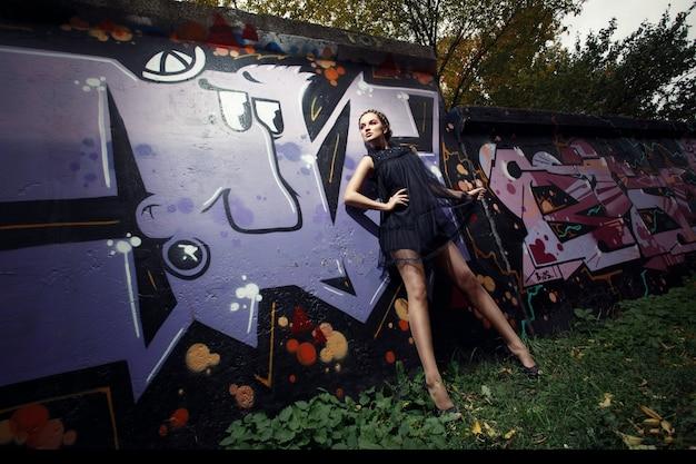 Женщина, прислонившись к стене с граффити