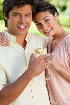 Женщина, прислонившись к другу, пока они касаются бокалов шампанского