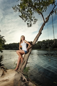 Woman leaning against a tree beside a lake