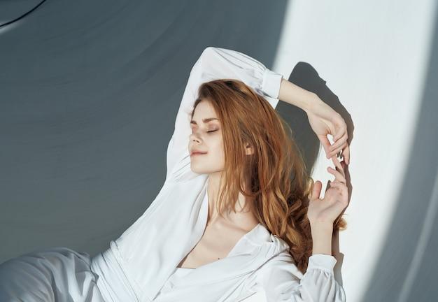 グラマーモデルのポーズをとる白いドレスで壁にもたれて女性