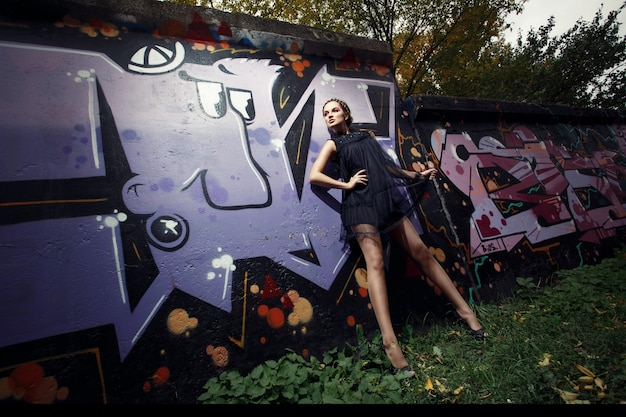 Woman leaning against a wall with graffiti