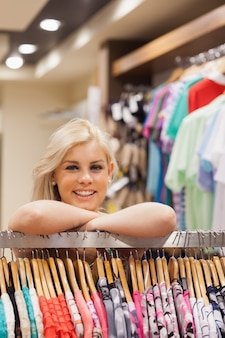 Woman leaning at a clothes rack while smiling