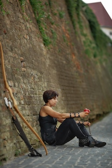Woman leaning on brick wall near bow and arrow.