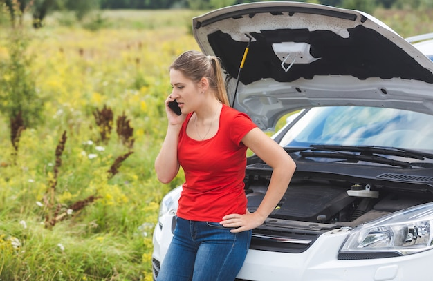 Woman leaning on broken car and calling for help by mobile phone
