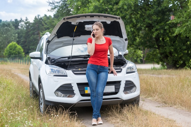 Woman leaning on broken car in field and calling for help on mobile phone