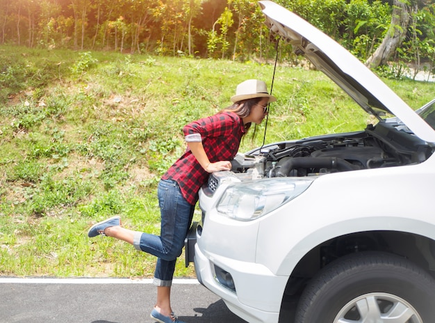Woman leaning over checking her car engine after breaking down