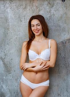 Donna appoggiata al muro di cemento con piante tropicali verdi intorno e posa in reggiseno e pantaloni bianchi