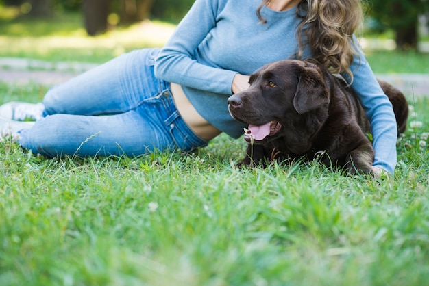 Woman leaning on dog over green grass