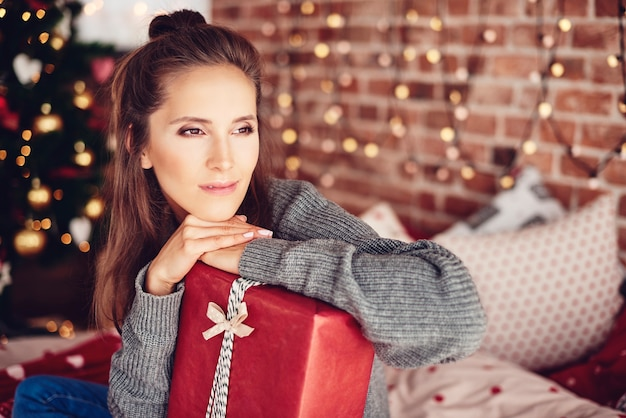 Donna che si appoggia su un regalo