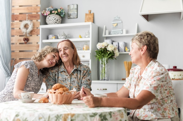Woman leaning head on her granny's shoulder during breakfast